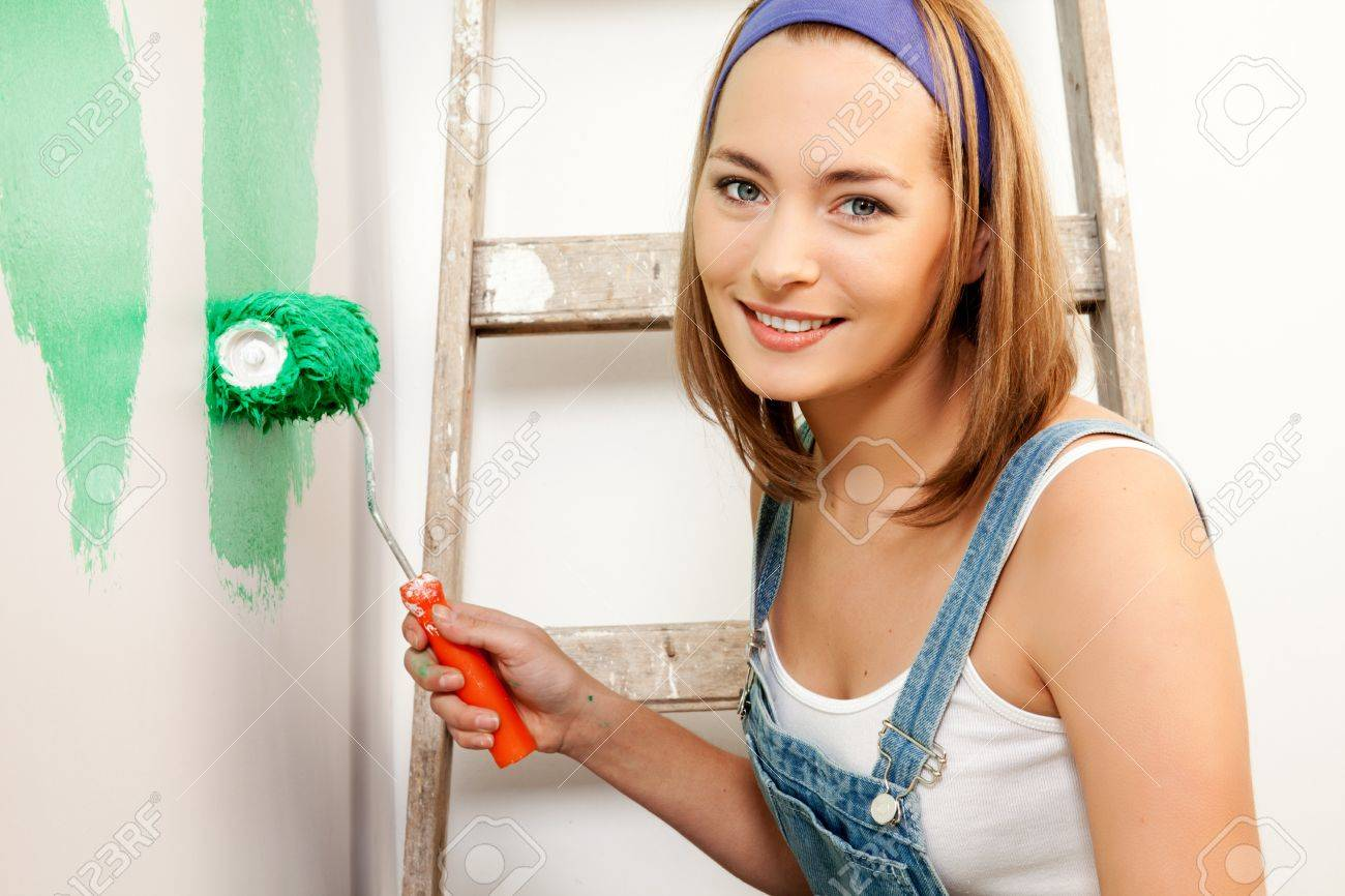 A woman with a roller brush, paiting the wall doing home improvements Stock Photo - 9600099