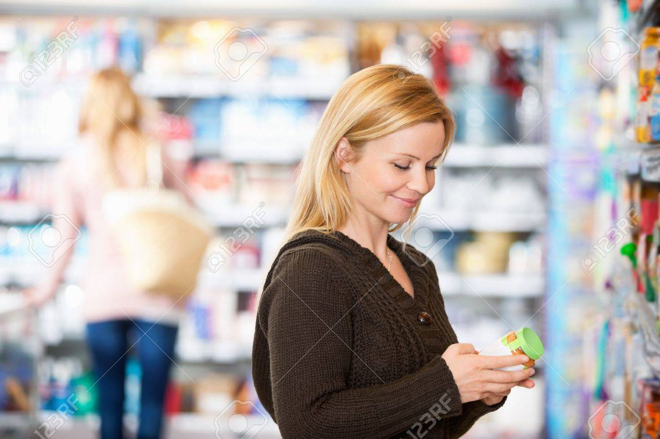 Young woman smiling while shopping in the supermarket with people in the background Stock Photo - 9887459