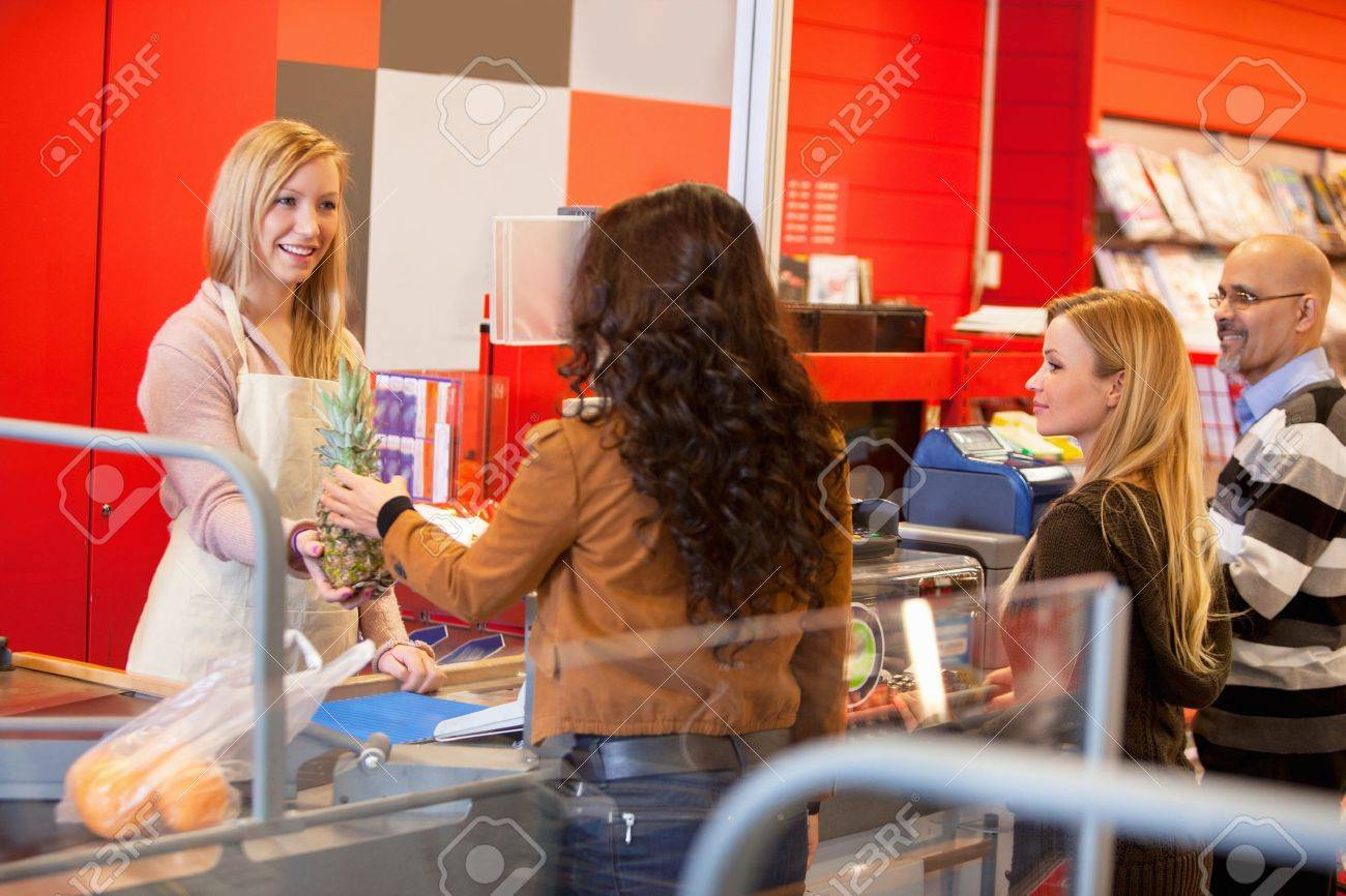View of happy shop assistant with customer in supermarket holding pineapple Stock Photo - 9886882