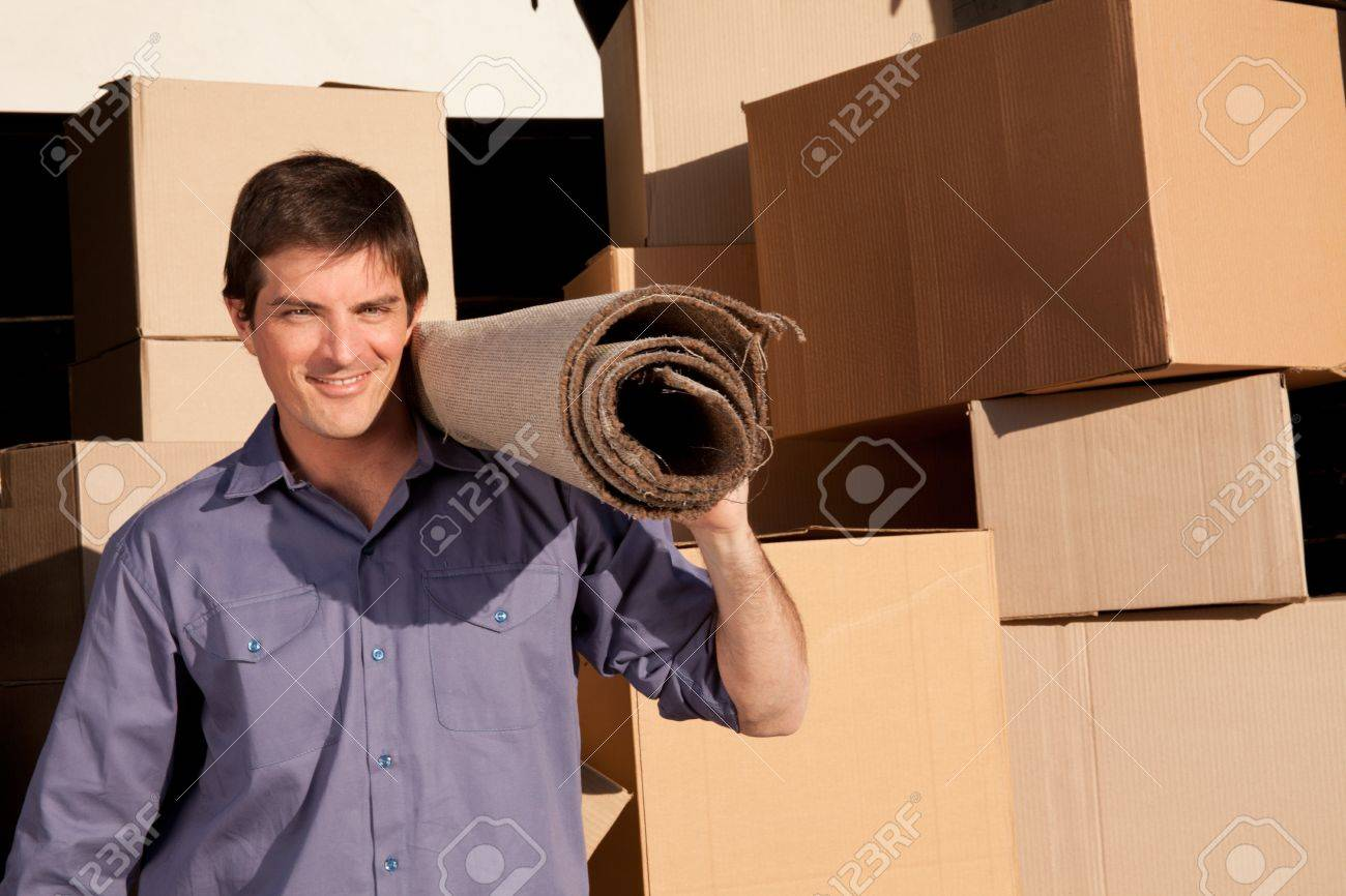 A moving an carrying a carpet with cardboard boxes in the background Stock Photo - 9887295