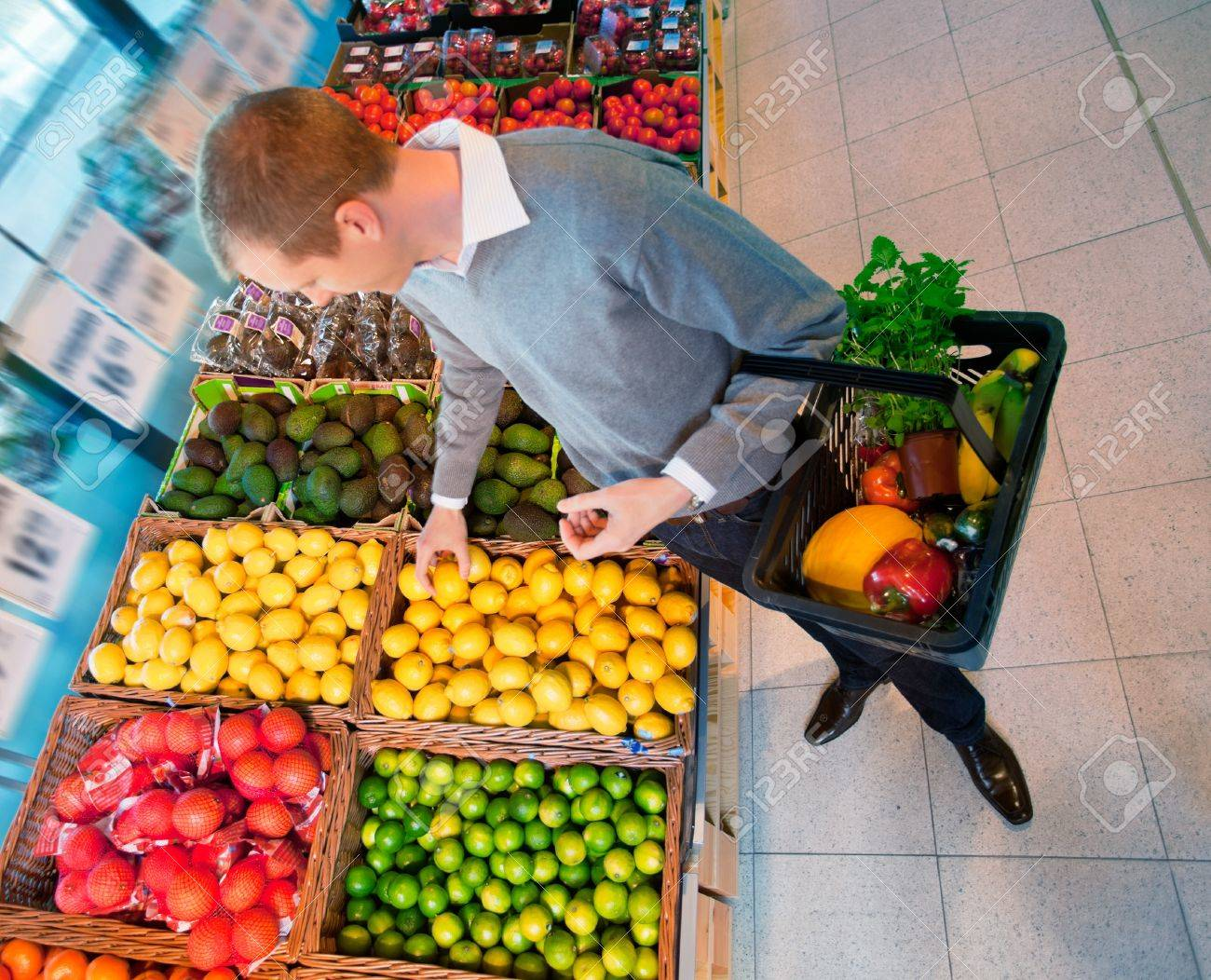 High angle view of a man carrying basket while buying fruits in the supermarket Stock Photo - 9887406