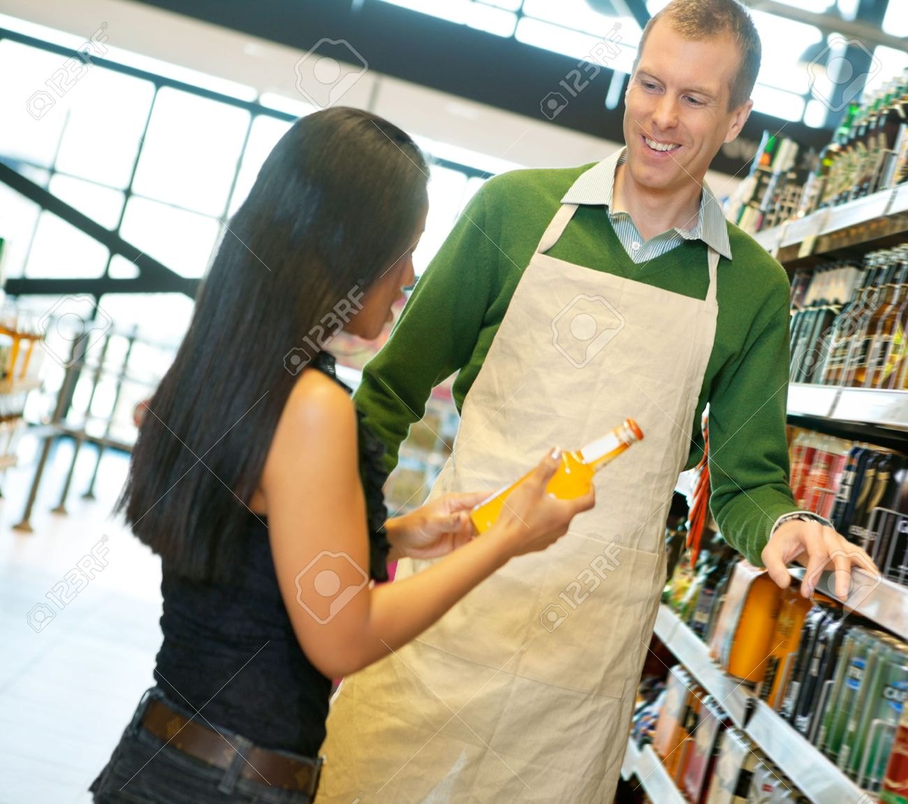 Woman standing with smiling store worker while holding drink bottle in grocery store Stock Photo - 10033226