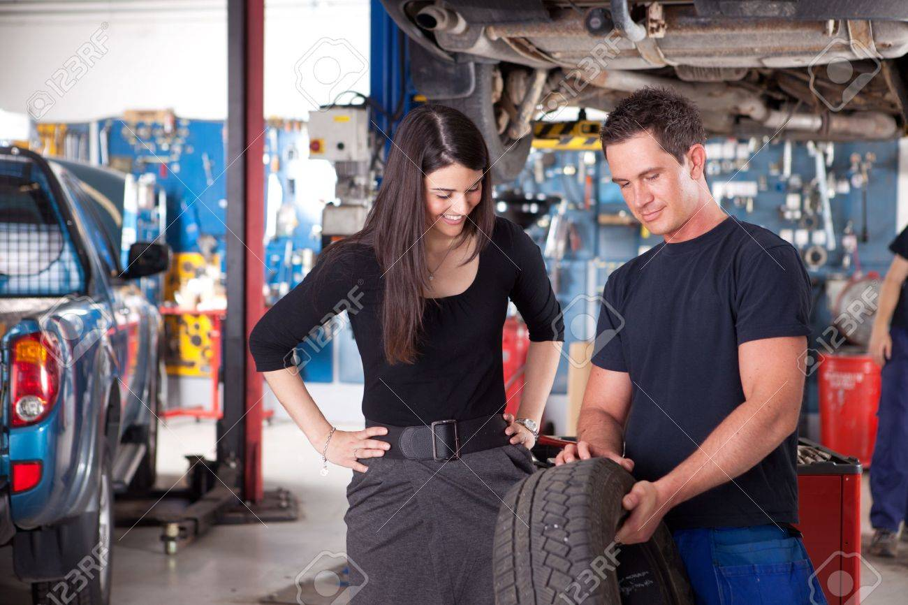 A mechanic showing the tread of a tire to a female customer Stock Photo - 10177877