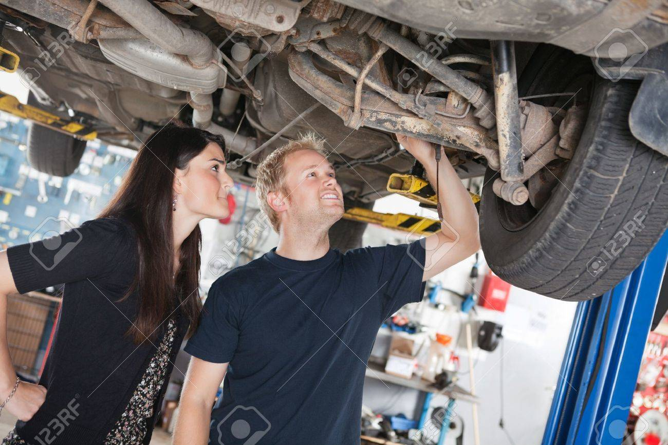 Young Mechanic And Woman Looking At Machine Of Car In Auto Repair – Machine Mechanic