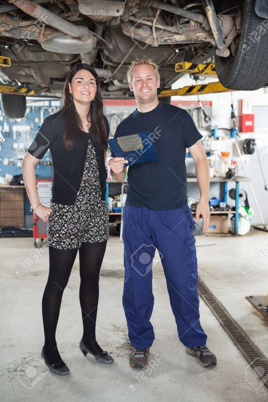 Portrait of young mechanic standing with female customer in auto repair shop Stock Photo - 10337067
