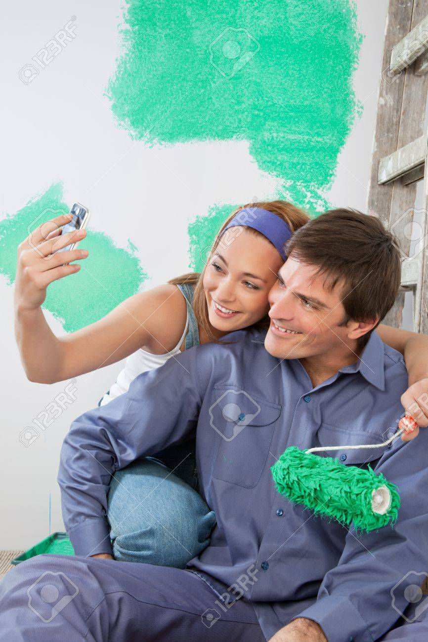 sweet young couple taking self portraits while holding color