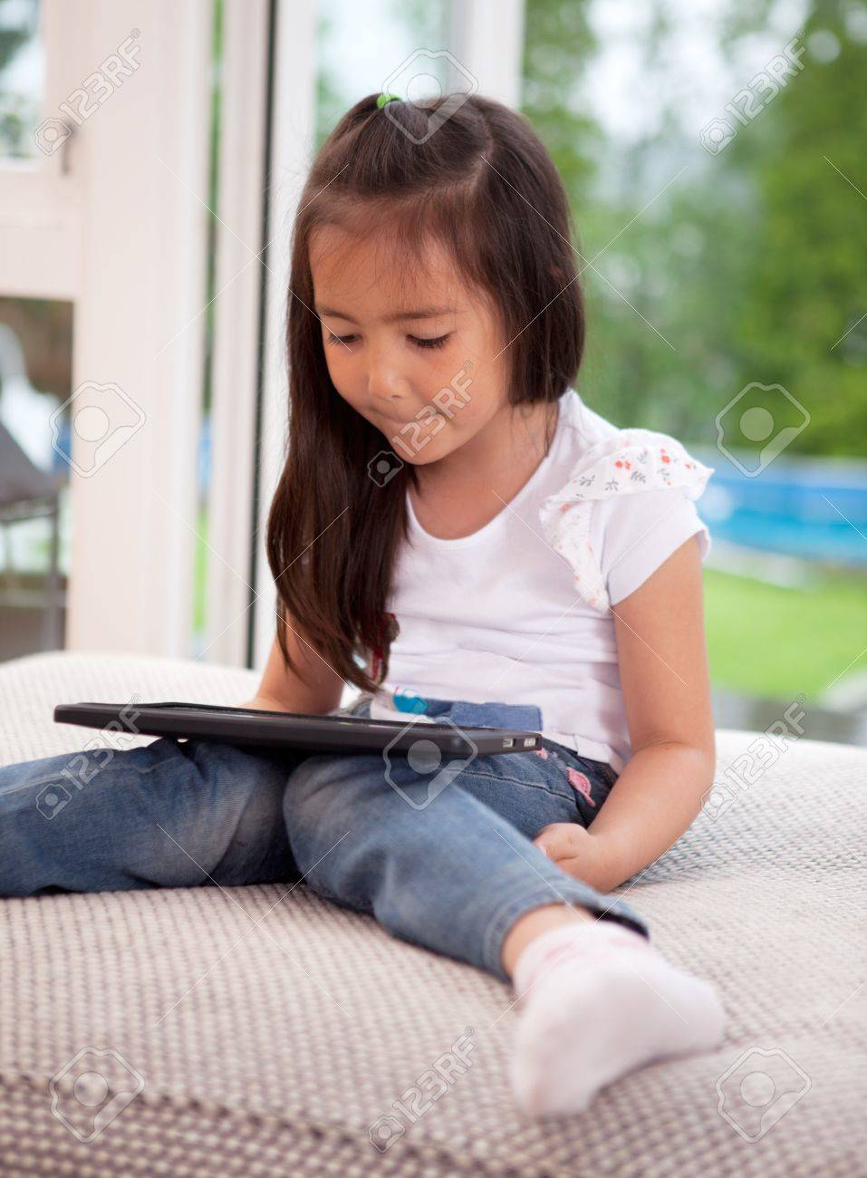 Young girl child looking at a digital tablet sitting on a couch cushion Stock Photo - 10393419