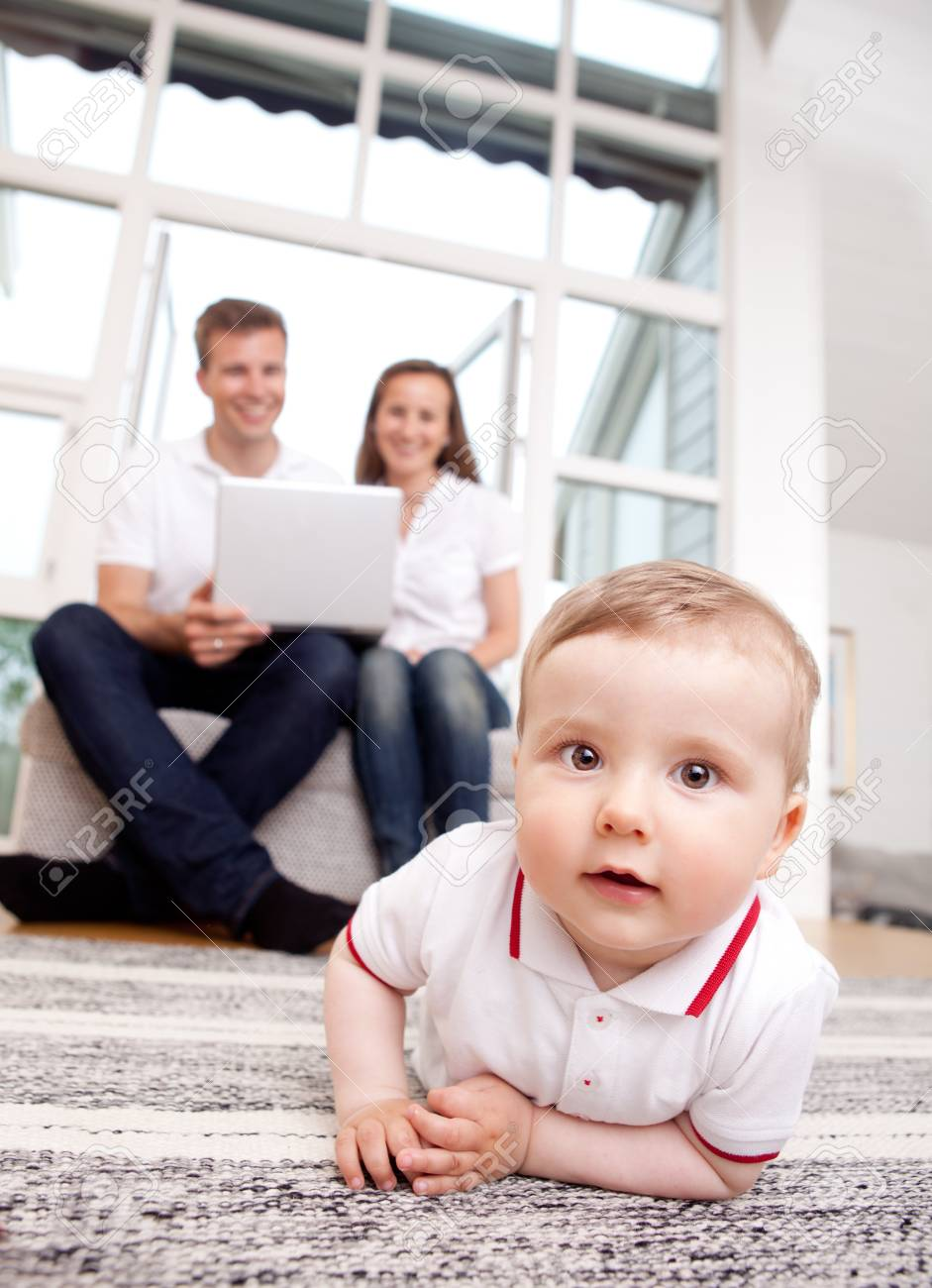 A happy curious young baby boy with parents in the background using computer Stock Photo - 10393414