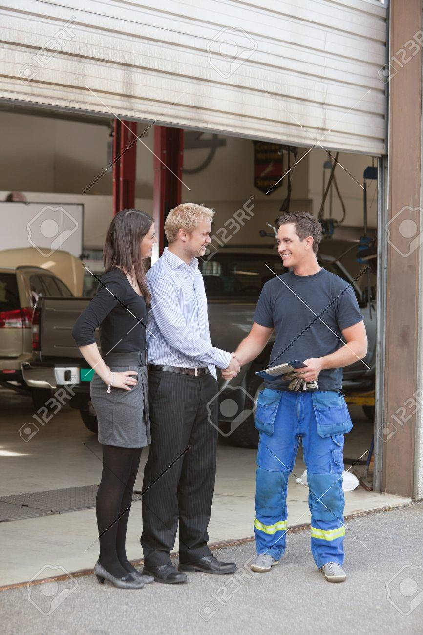 full length of mechanic shaking hands with client outside garage full length of mechanic shaking hands with client outside garage stock photo 10451918