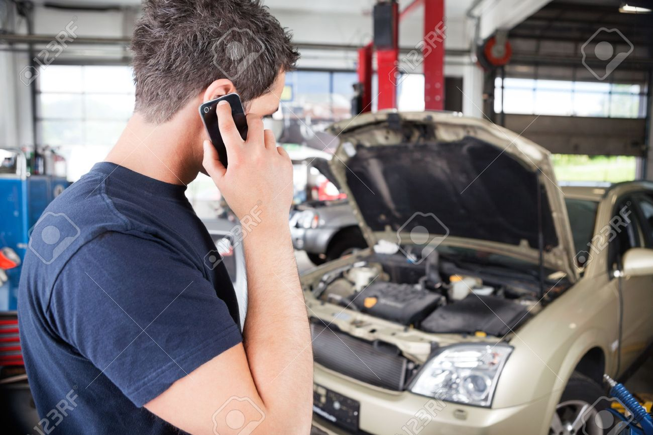 Mechanic talking on cell phone in garage Stock Photo - 10451911