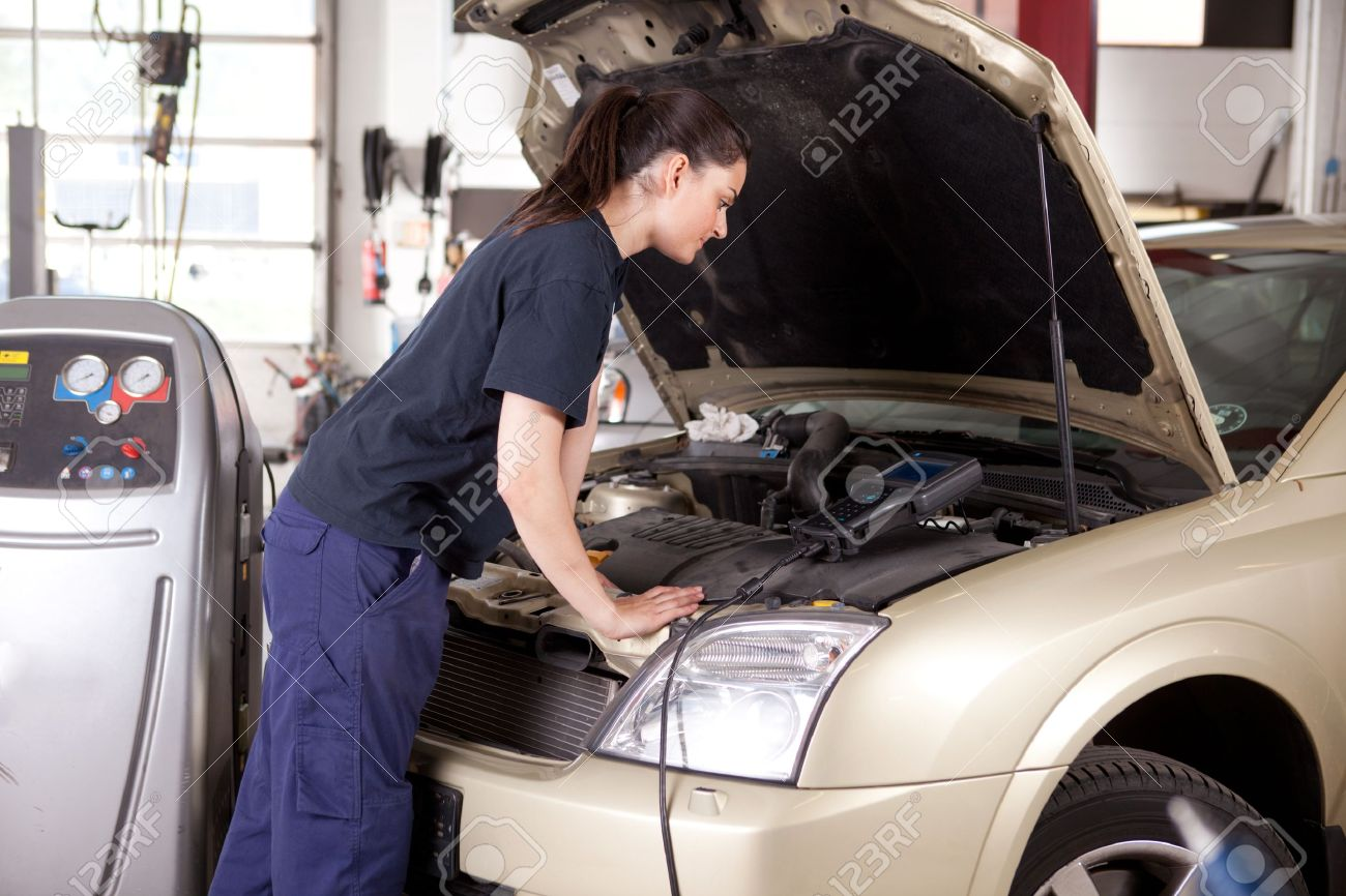 A woman mechanic tuning a car with diagnostic equipment Stock Photo - 10480954