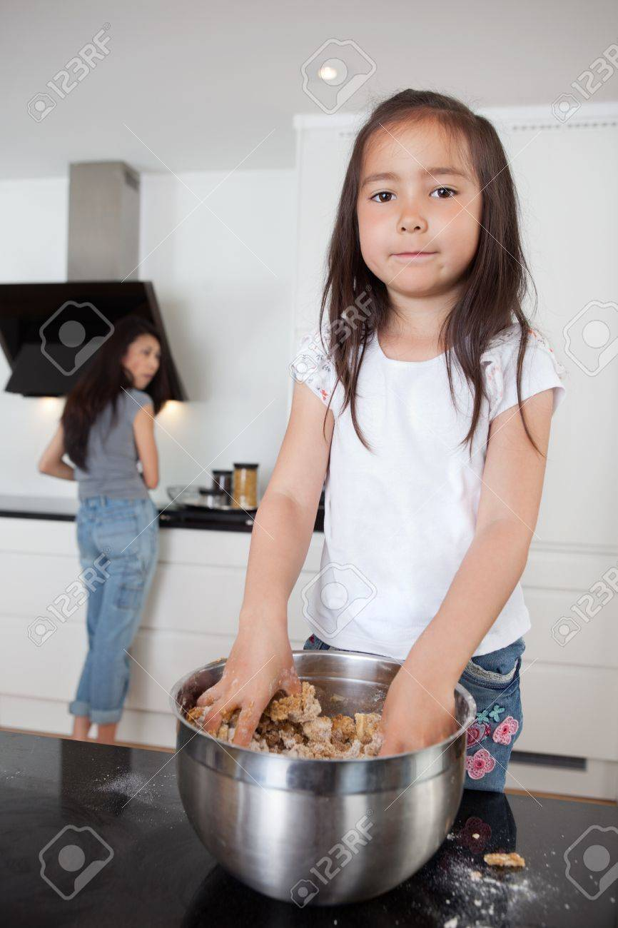 Cute girl mixing dough in kitchen with mother in background Stock Photo - 10536610