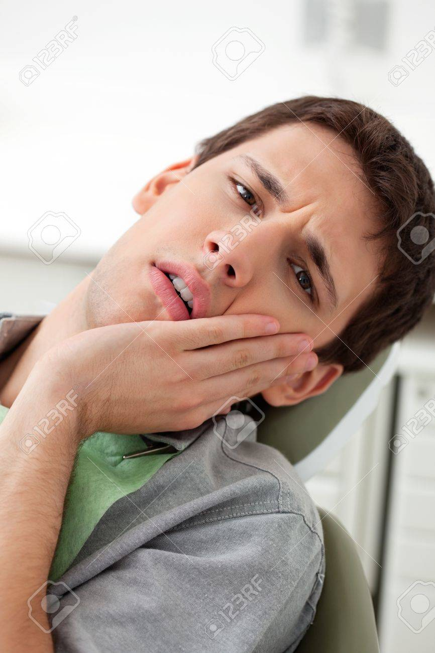 Young man holds his mouth in pain Stock Photo - 10536713