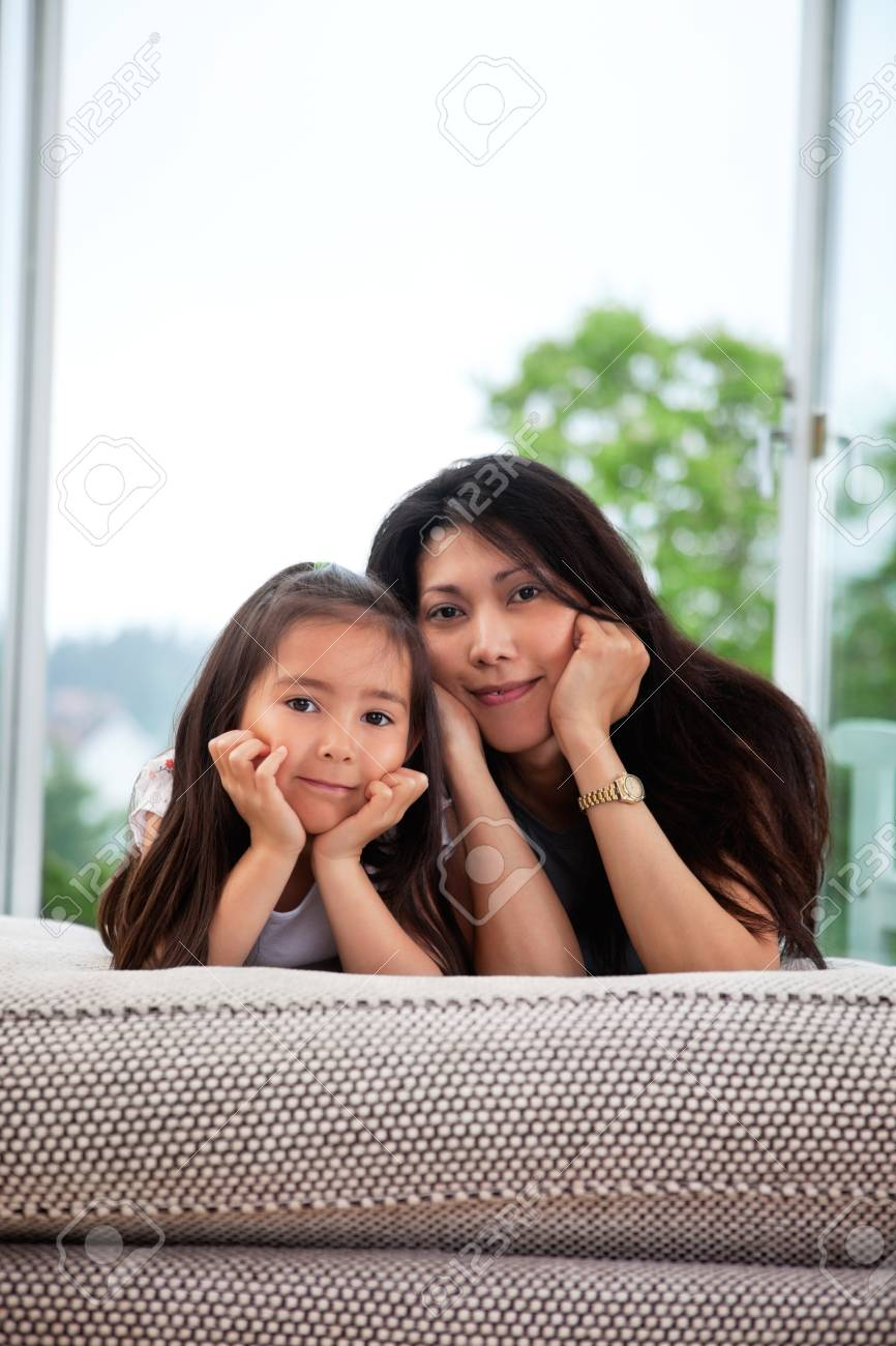 Portrait of young mother and cute daughter lying on a couch Stock Photo - 10536553