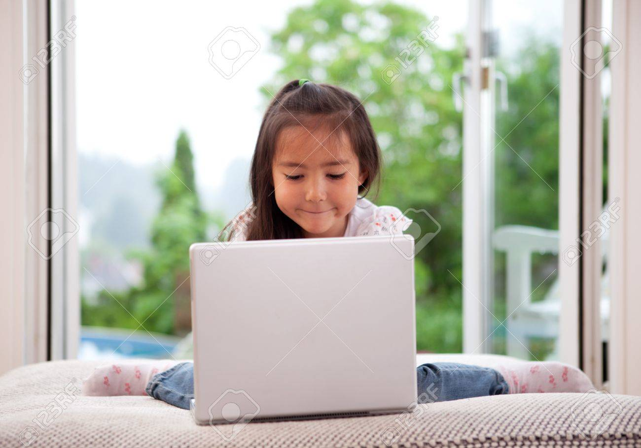 Young cute child using a computer in an indoor living room setting with large window Stock Photo - 10559752