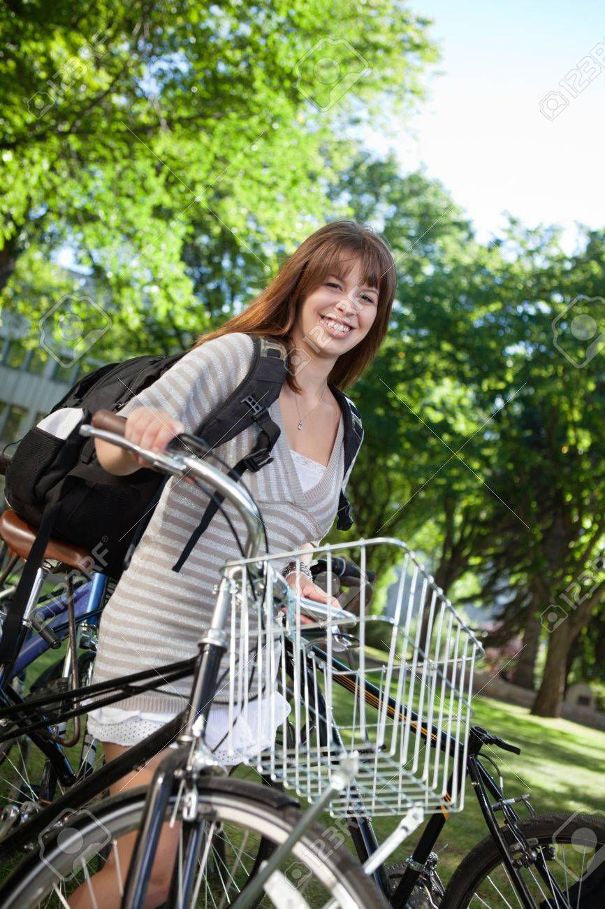 Portrait of a happy female student standing with her bike Stock Photo - 10762331