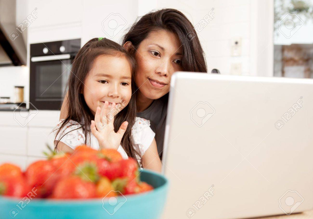 Mother and daughter using computer, waving while in a live video chat Stock Photo - 10988895