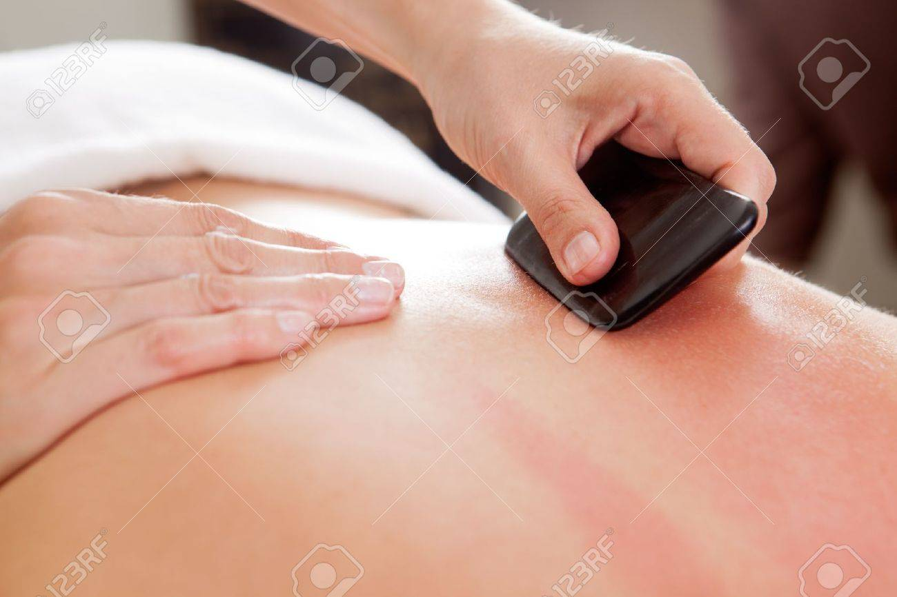 Large bone scraper tool being used ruing a guasha acupuncture treatment Stock Photo - 10989206