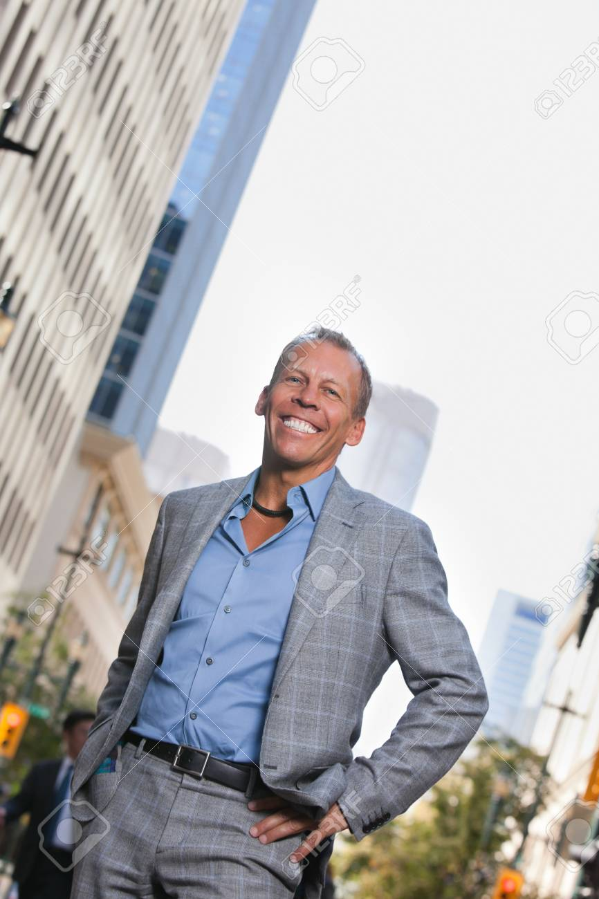 Smiling mature businessman standing with buildings in background Stock Photo - 11048289