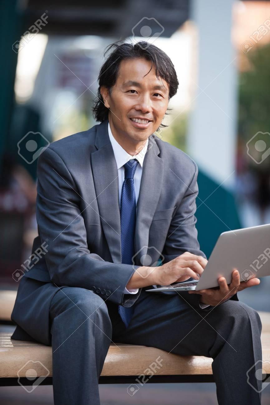 Portrait of smiling businessman using laptop outdoors Stock Photo - 11048310
