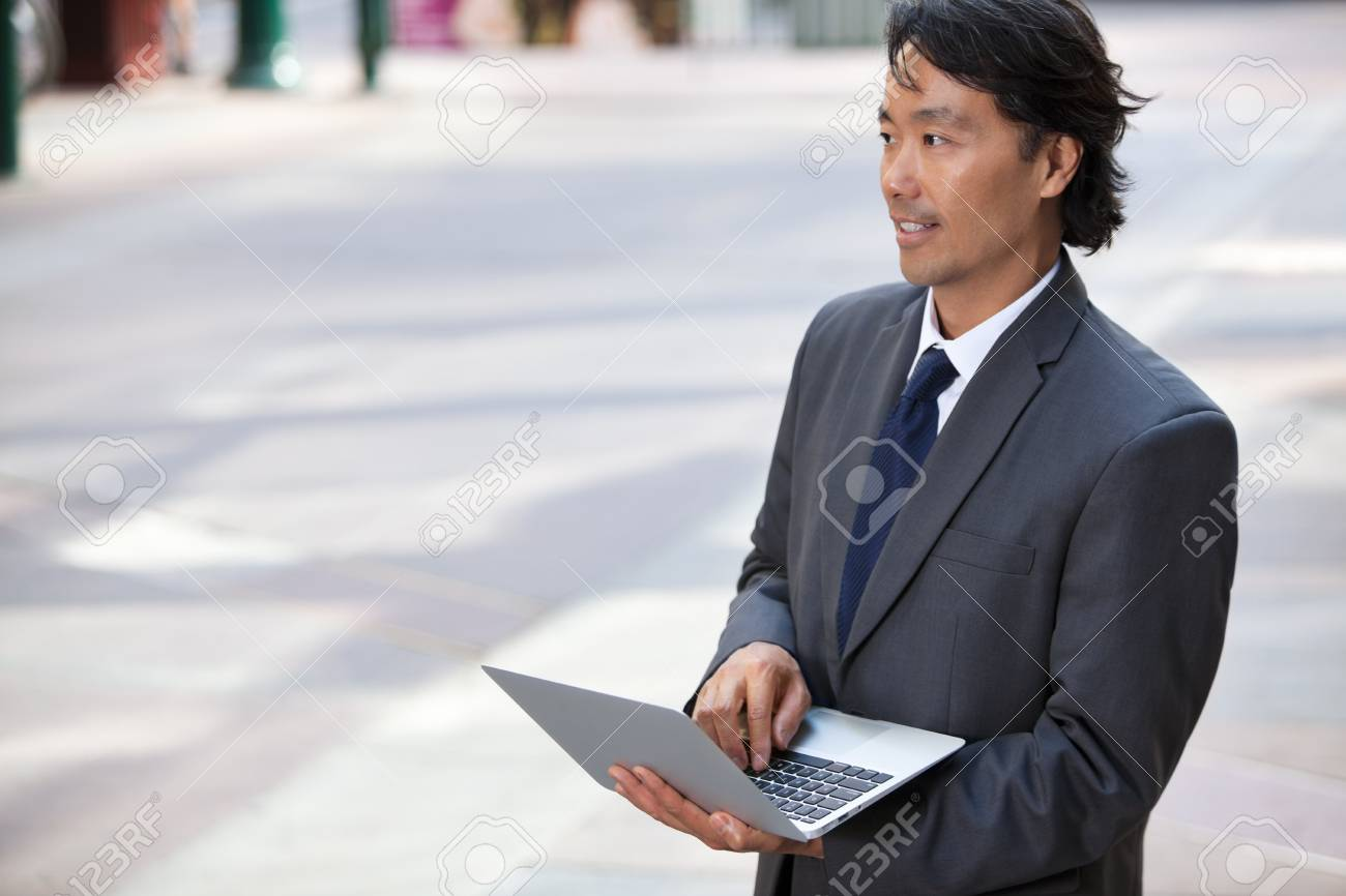 Handsome businessman using laptop outdoors Stock Photo - 11048124