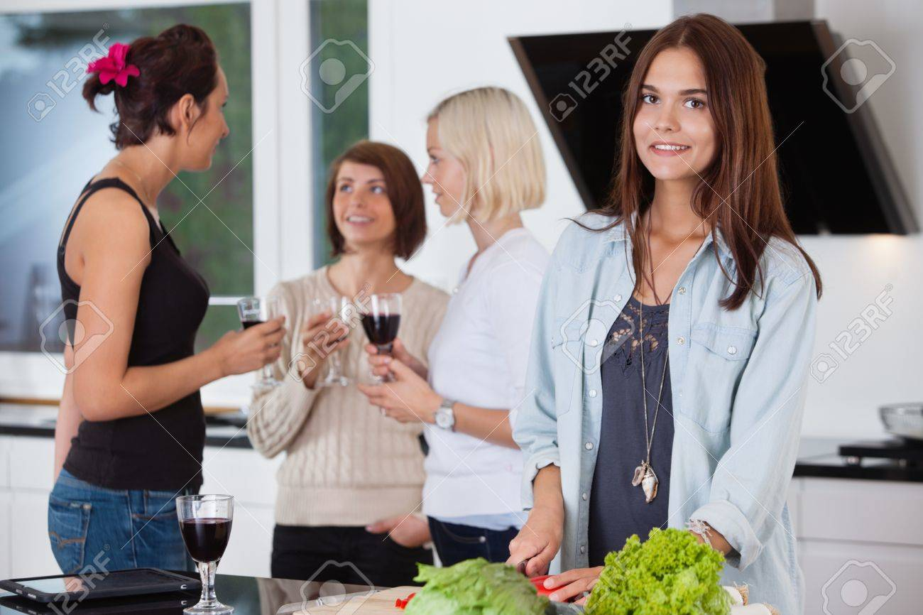 Portrait of pretty female cutting vegetables while her friends having drink in background Stock Photo - 11048253