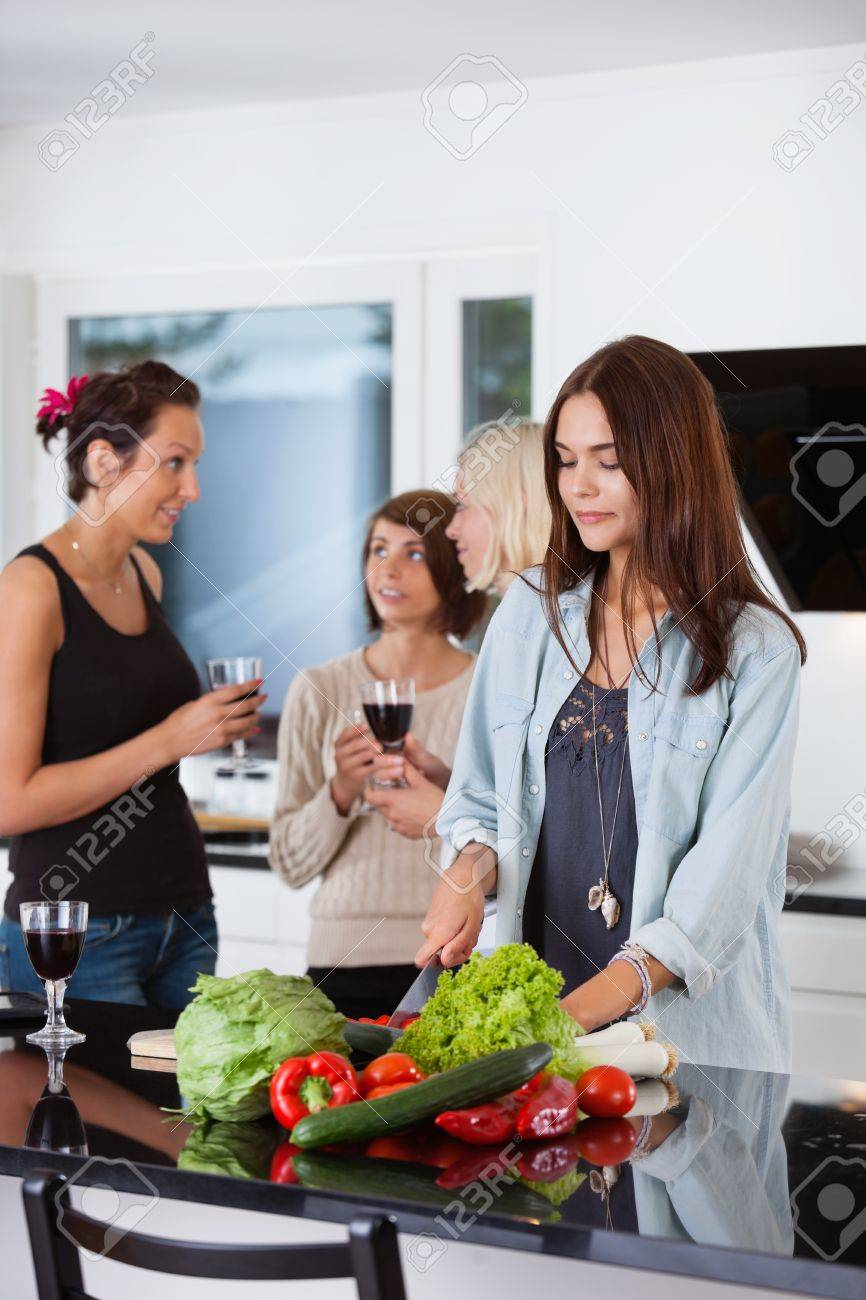 Pretty female cutting vegetables while her friends having drink in background Stock Photo - 11173379