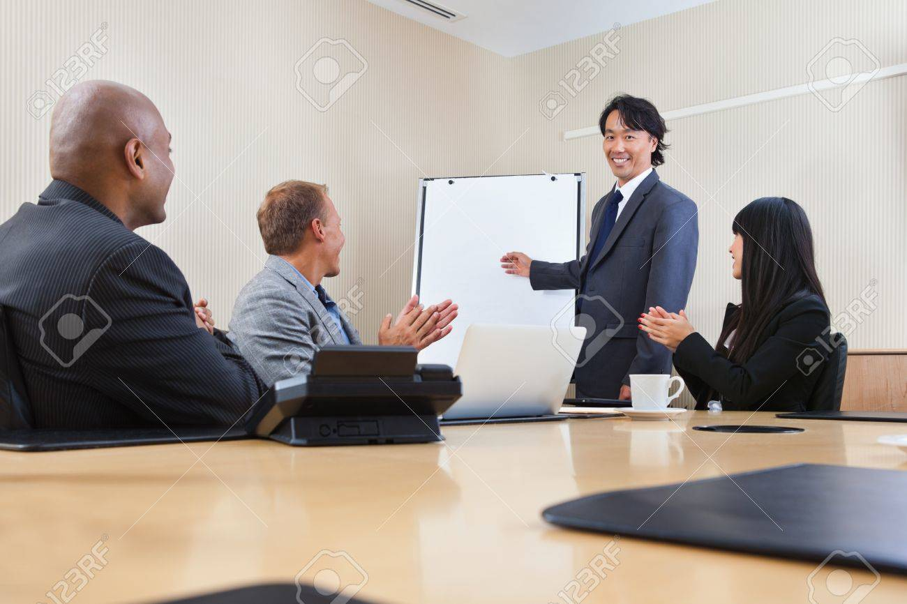 Smiling Business Man Giving A Presentation To Associates