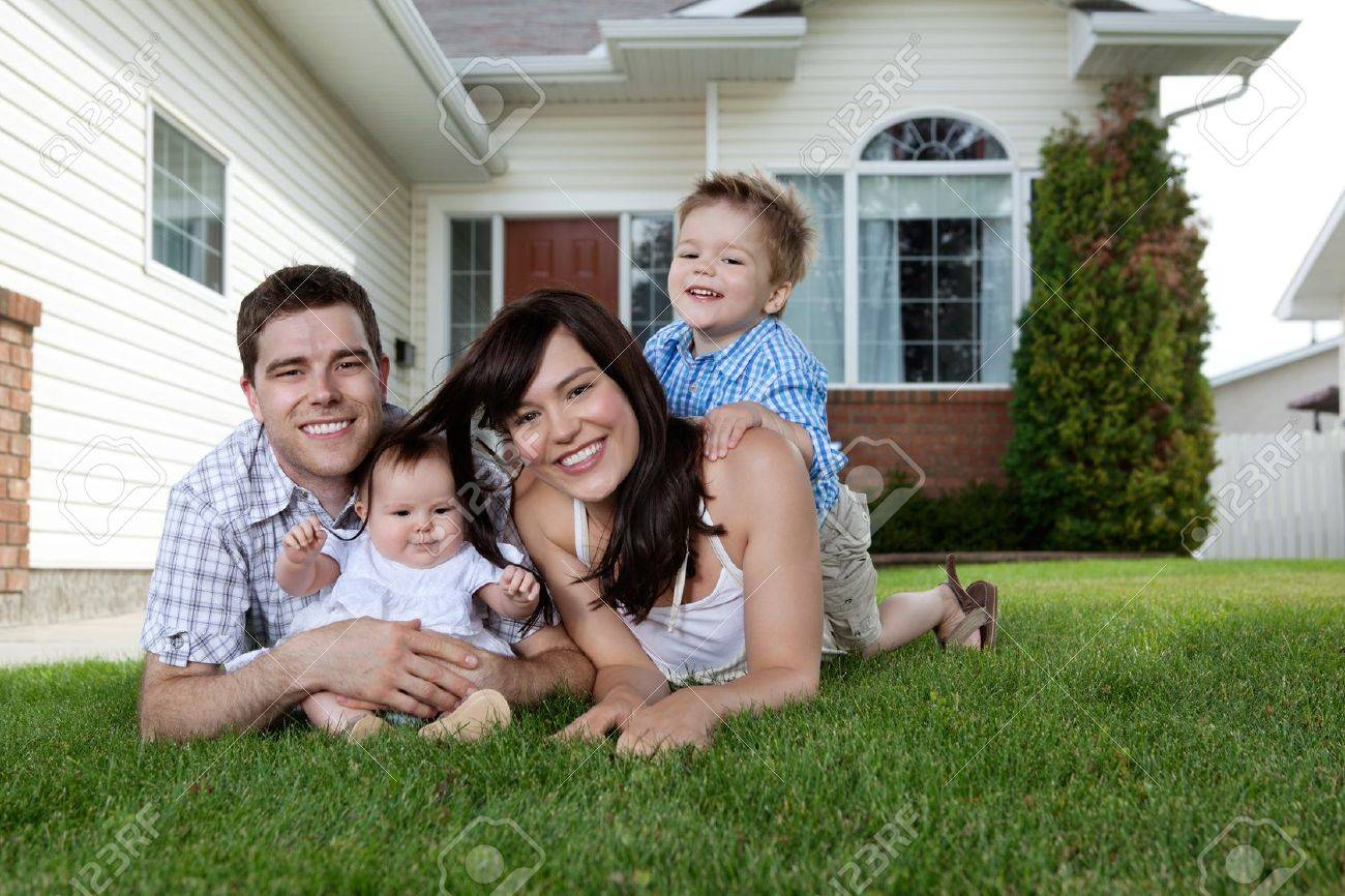 Happy couple lying down on grass with their adorable children Stock Photo - 11538776