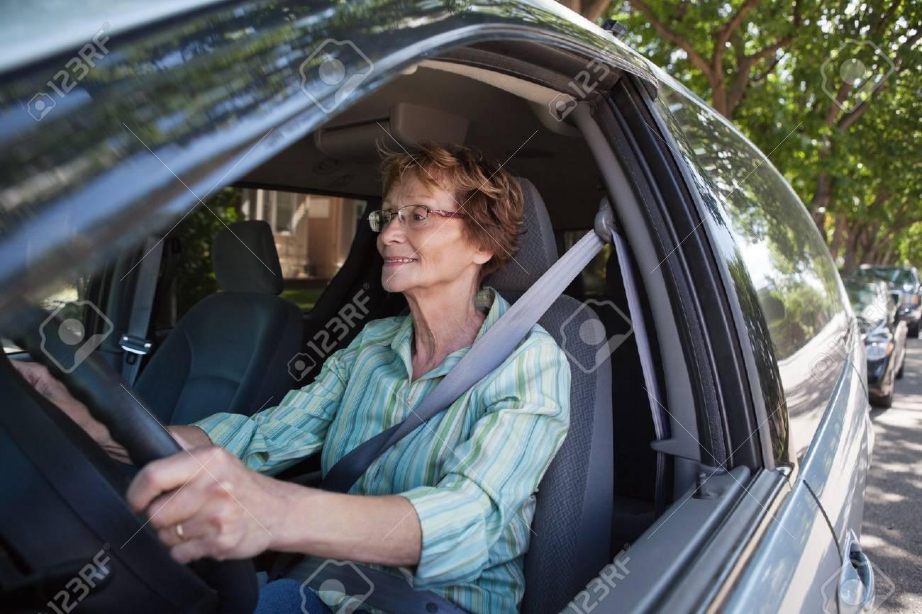 Active senior woman smiling while driving car - 11538752