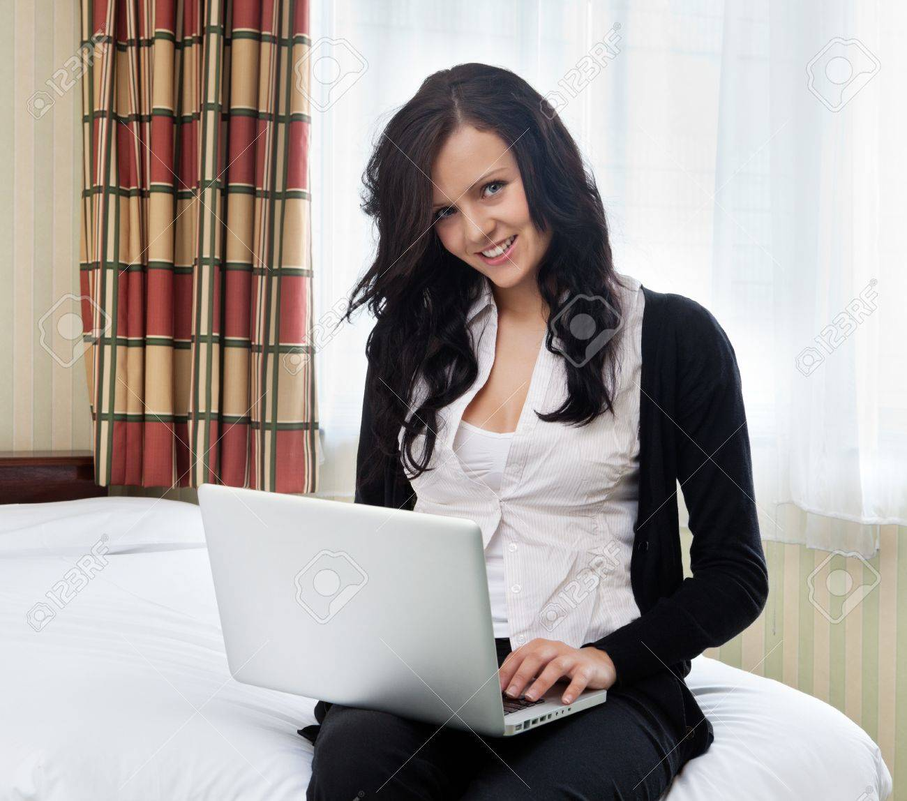 Portrait of beautiful businesswoman using laptop sitting in hotel room Stock Photo - 11538632