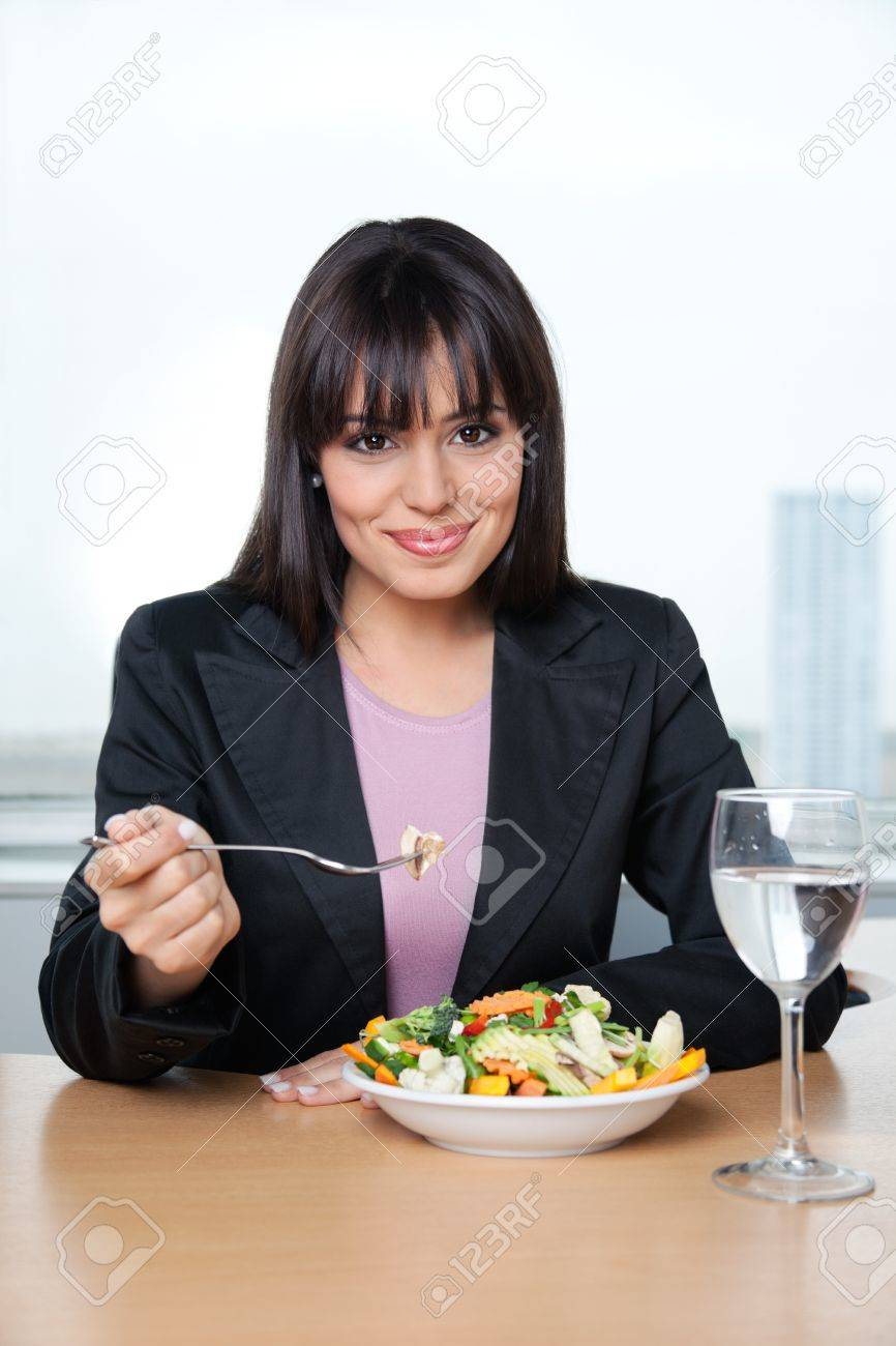 Portrait of smiling female executive having fresh vegetable salad in office Stock Photo - 11702314