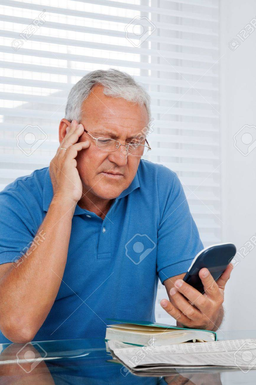 Serious senior man looking at calculator Stock Photo - 11702358