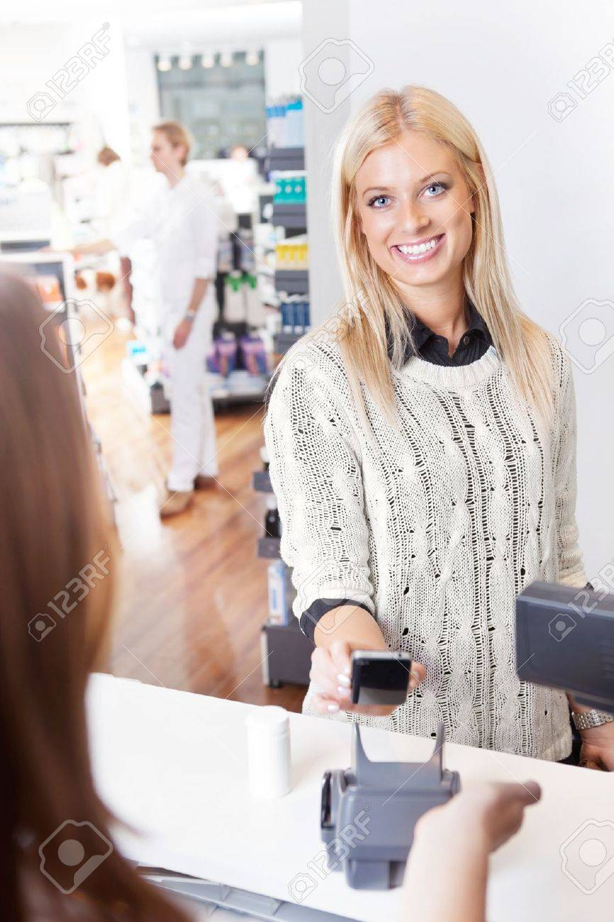 Female customer using cell phone to pay for goods Stock Photo - 11702366