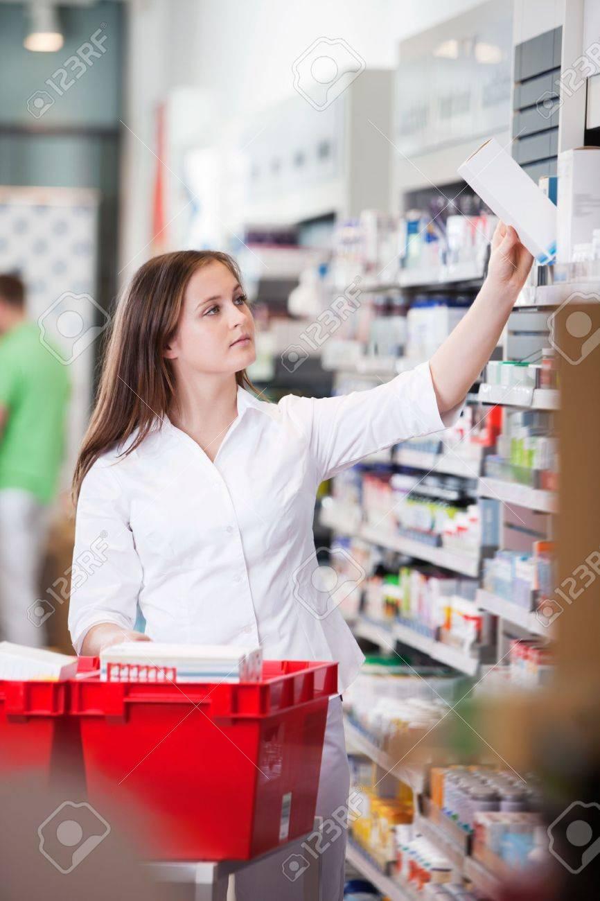 female pharmacist keeping medicine box on the shelf at drugstore female pharmacist keeping medicine box on the shelf at drugstore stock photo 11702367