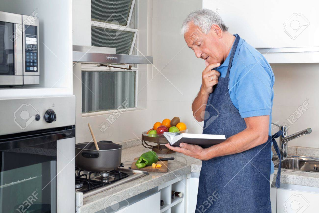 Senior man preparing food with the help of recipe book stock photo senior man preparing food with the help of recipe book stock photo 11702388 forumfinder Image collections