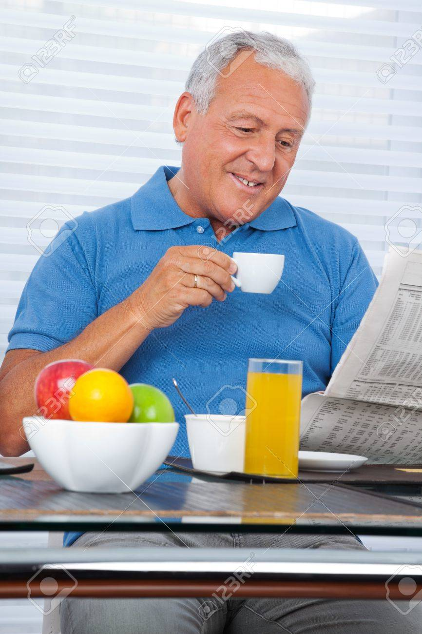 Smiling senior man reading newspaper while having breakfast at home Stock Photo - 11702396