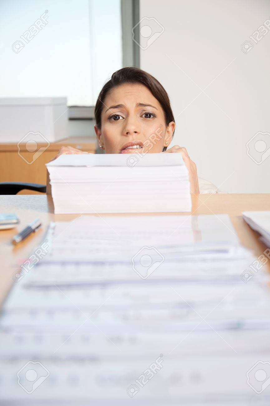 Head of businesswoman behind large pile of papers Stock Photo - 11702429