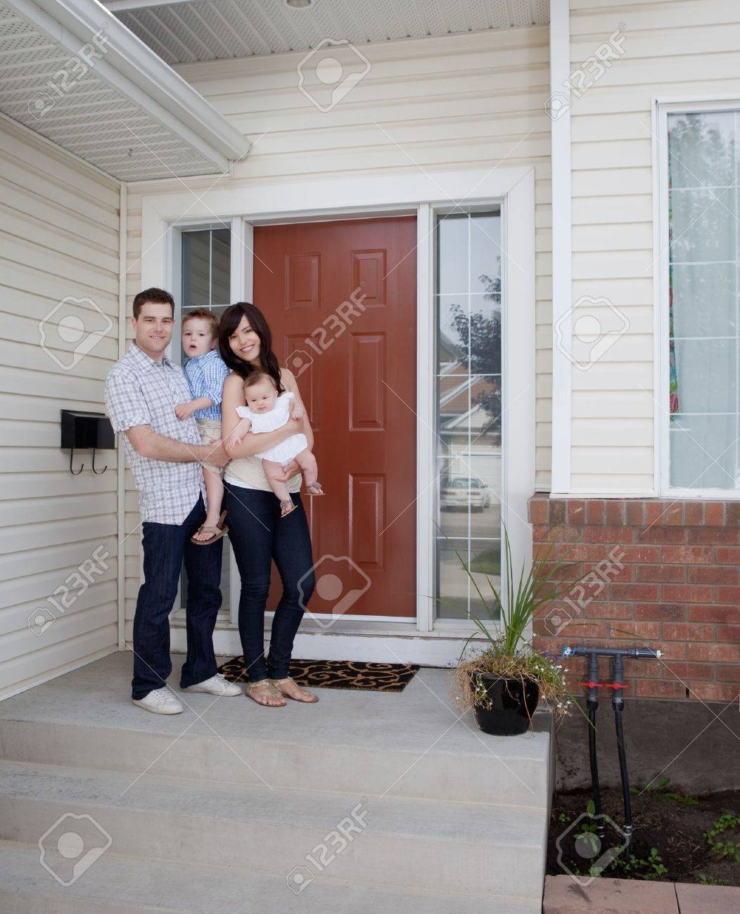 Portrait of young family standing in front of house Stock Photo - 12382325