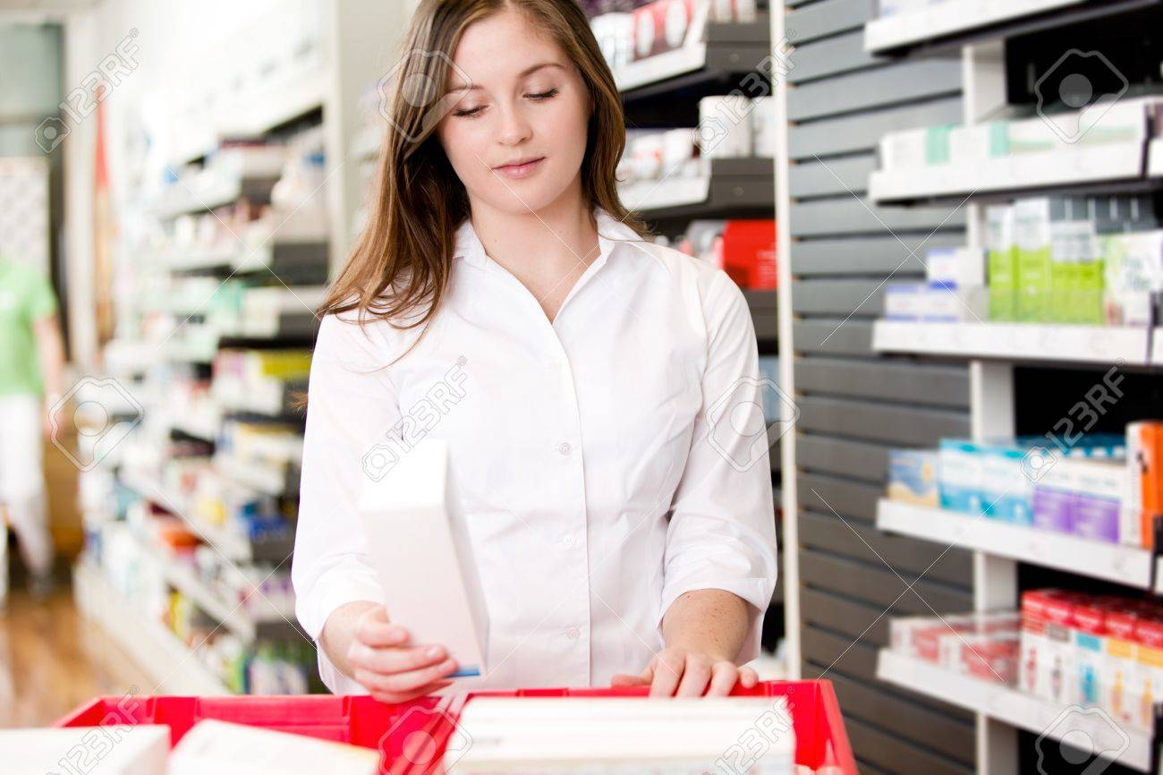 Pharmacist stocking shelves in pharmacy with box of medicine - 12382239