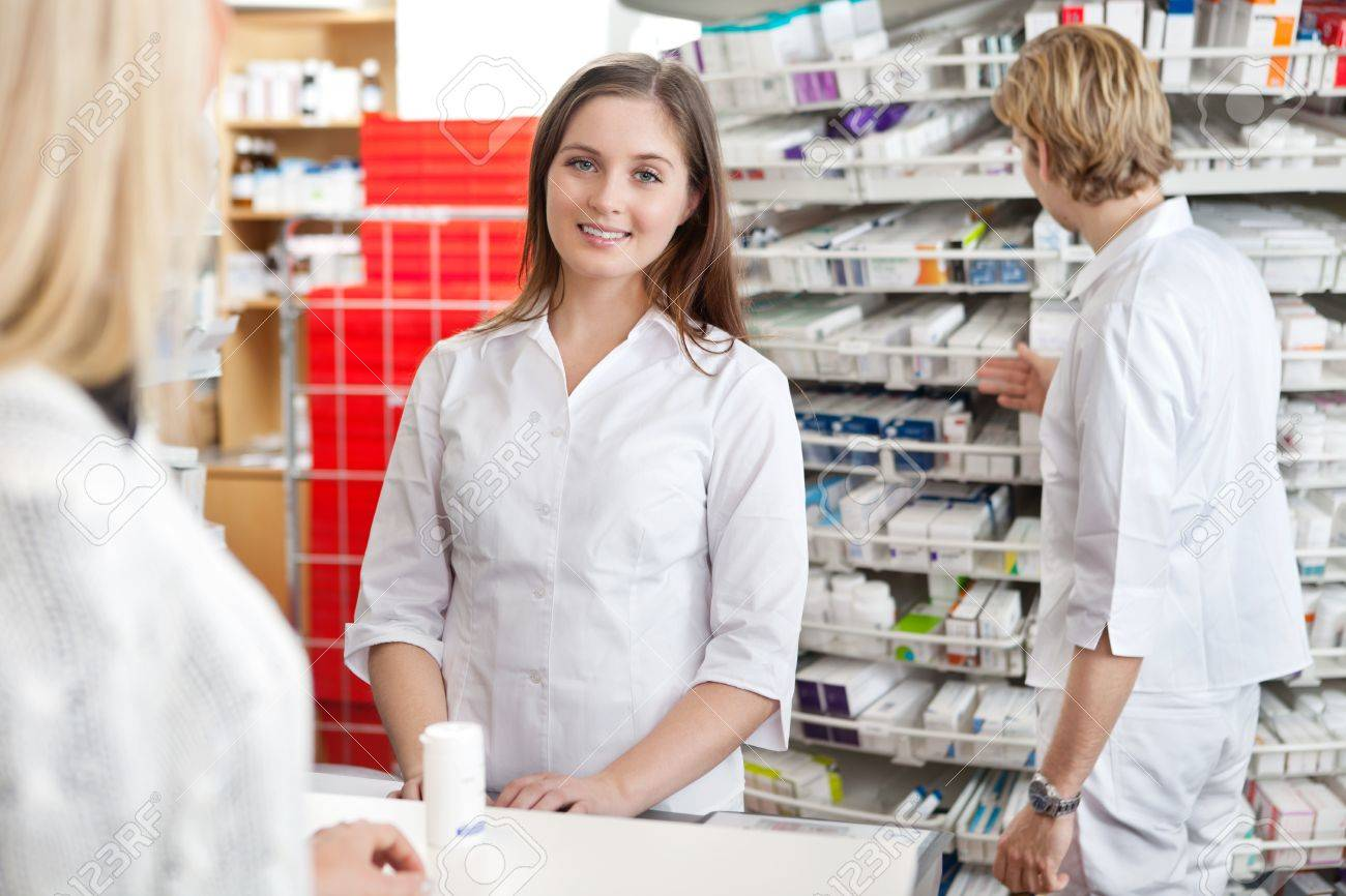Pharmacist smiling while attending customer at counter - 12766930