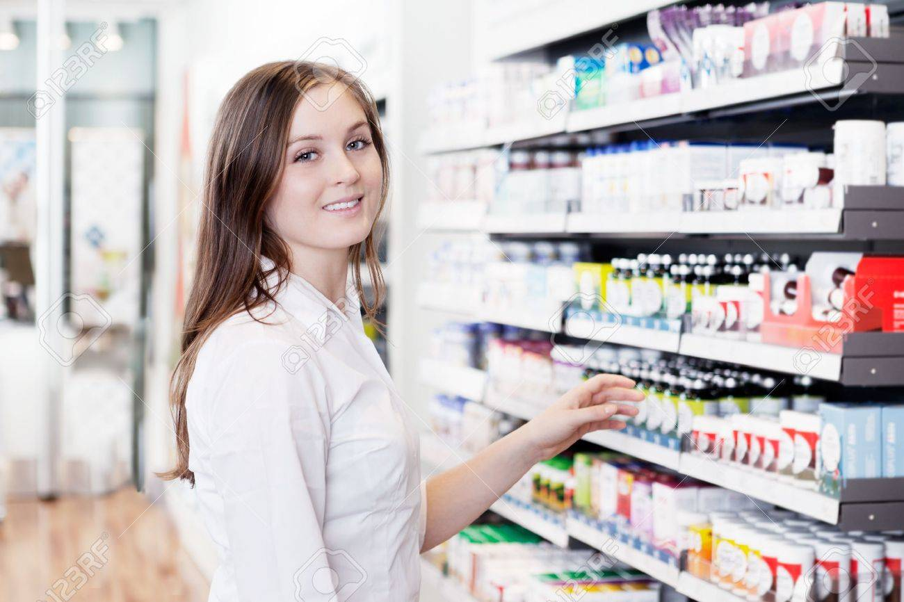 Portrait of young female pharmacist standing in pharmacy store - 12766908
