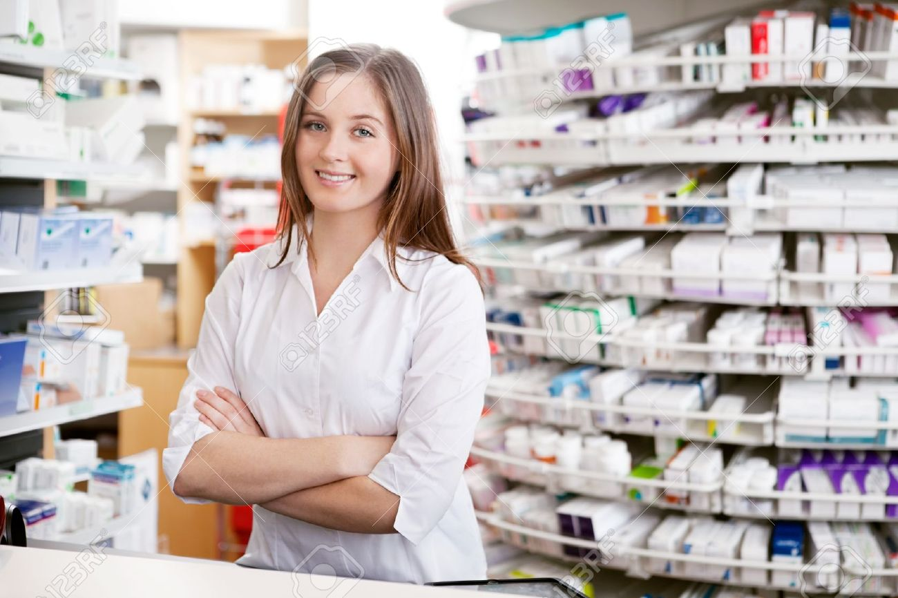 Portrait of female pharmacist standing with arms crossed at counter in pharmacy - 13264530