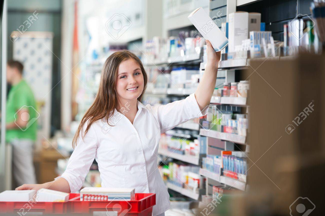 portrait of female pharmacist keeping a box on shelf stock photo portrait of female pharmacist keeping a box on shelf stock photo 13264520