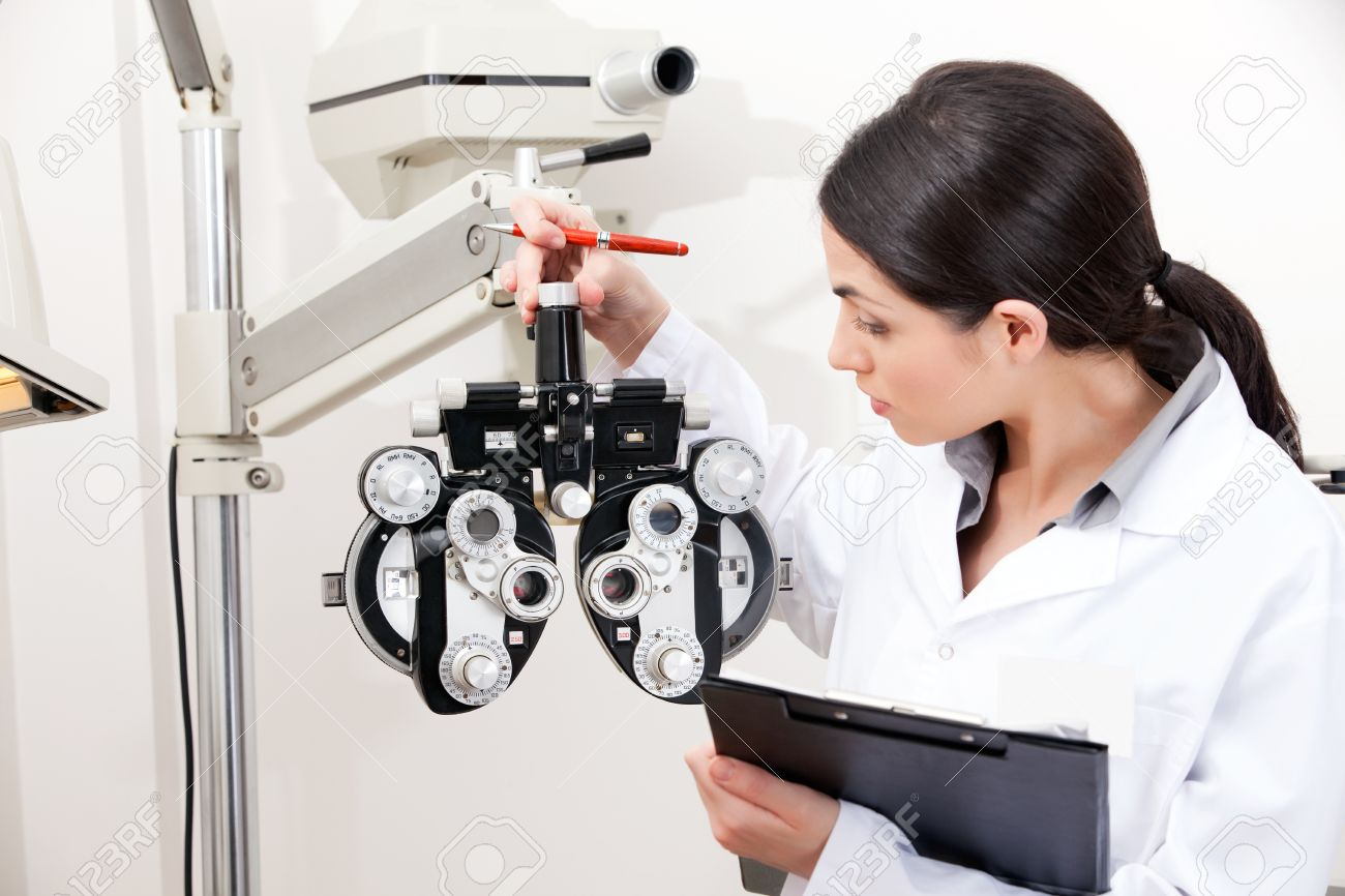 Female optometrist looking at phoropter Stock Photo - 13264072