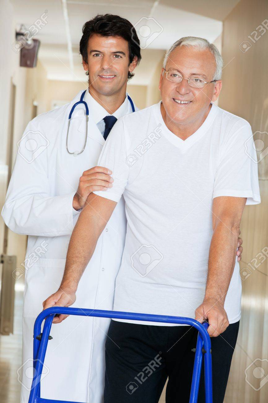 Young happy doctor helping an old man with his walker Stock Photo - 13800150