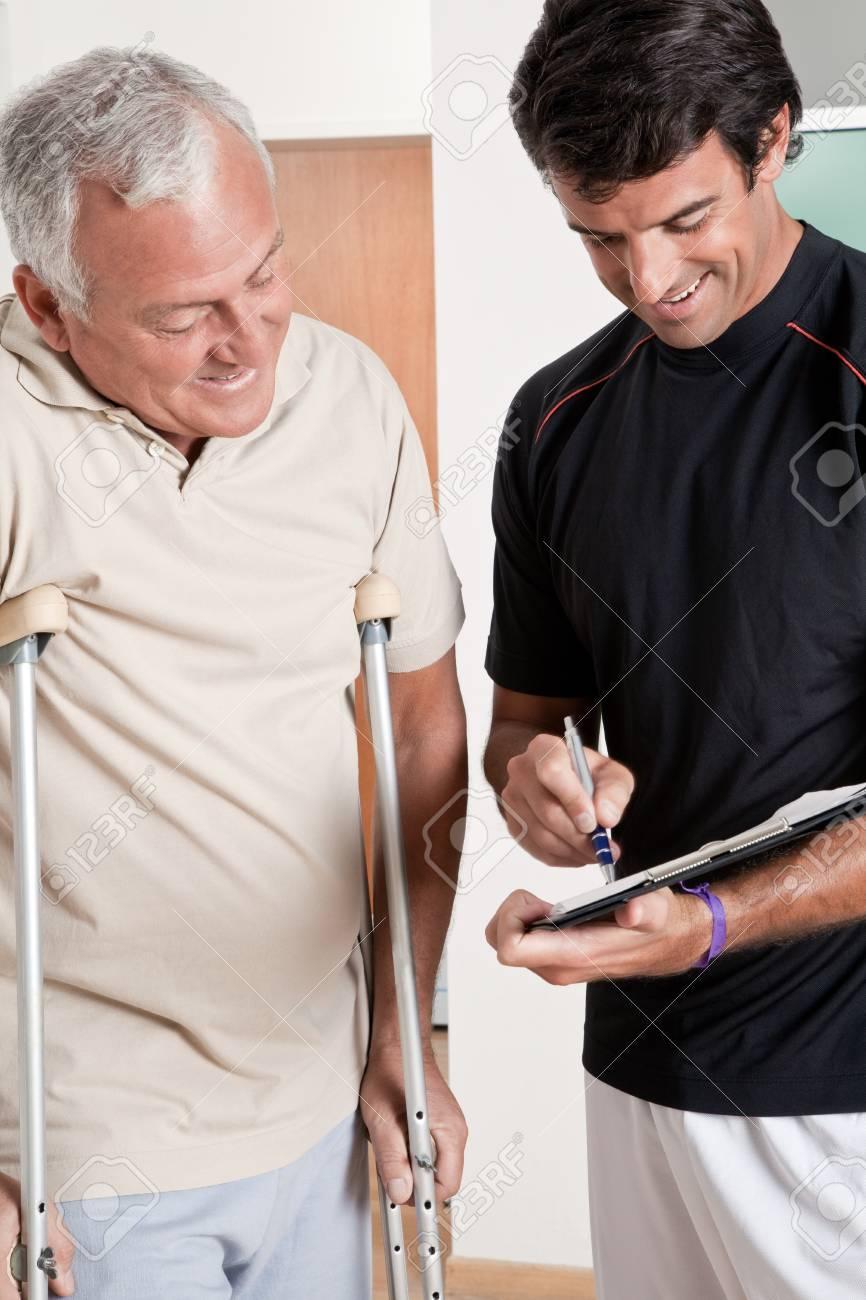 Patient on crutches discusses his progress Stock Photo - 14172351