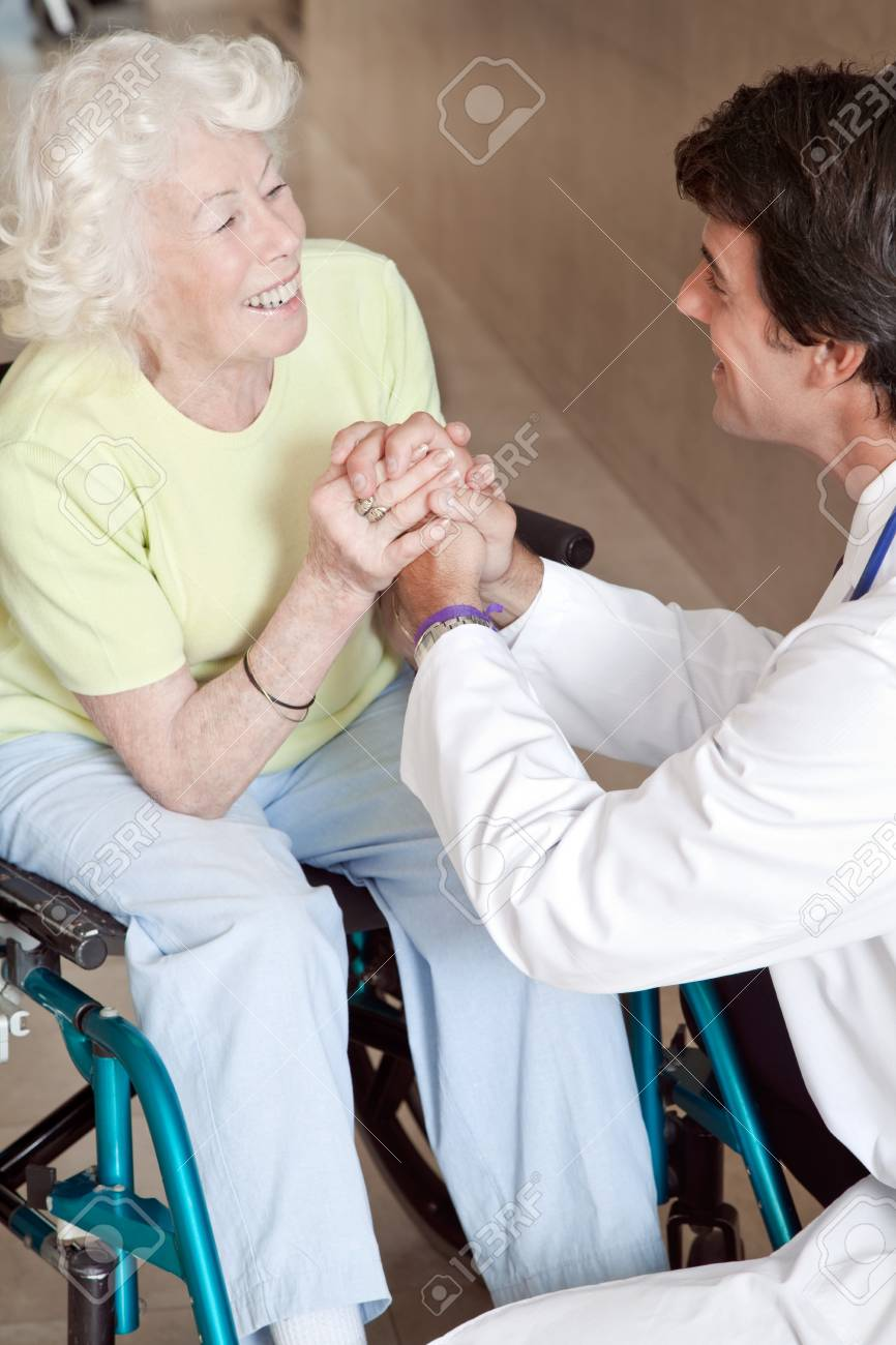 Doctor with patient on wheel chair at hospital Stock Photo - 14350854