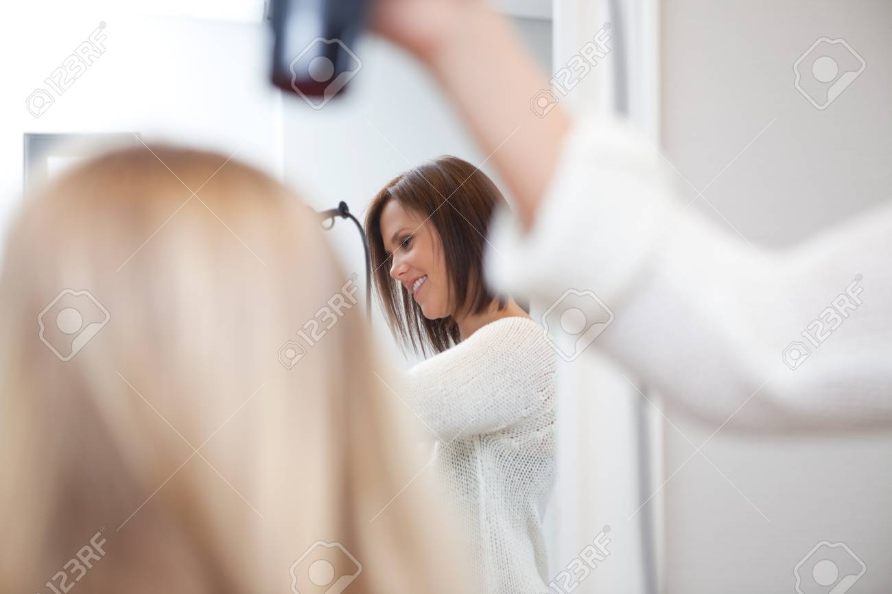Stylist drying womans hair in beauty salon Stock Photo - 14350804