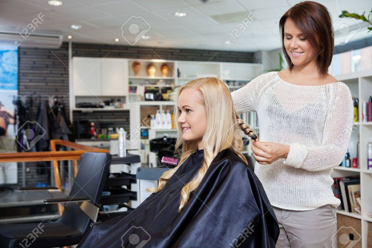 Young woman having her hair styled by beautician at parlor Stock Photo - 14454735